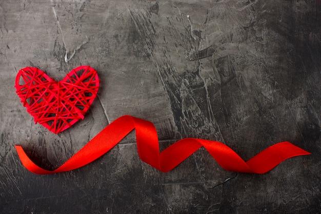 어두운 배경에 마음과 빨간 리본입니다. 발렌타인 데이 또는 결혼식. 위에서보기