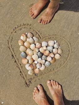 모래 남자와 여자의 발자취에 심장 ans 껍질