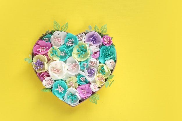 Heart of artificial flowers handmade on a yellow paper background.
