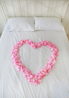 Heart of artificial pink rose petals on a bed