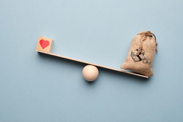 はかりにお金の袋を持った愛の象徴としての心。富の優先順位。