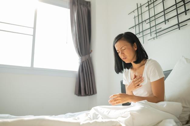 Концепция сердечного приступа, азиатская женщина не может работать, сегодня так устала. она больна серьезным и острым приступом сердечного ритма в постели. молодая женщина в пижаме с сердечным приступом в своей спальне.