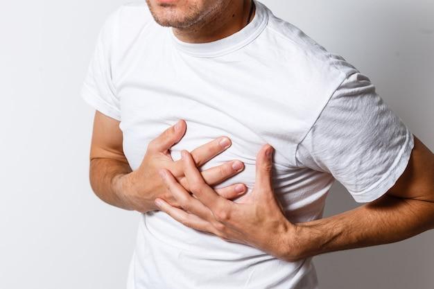 심장 마비 개념입니다. 가슴 통증으로 고통받는 젊은 남자, 클로즈업
