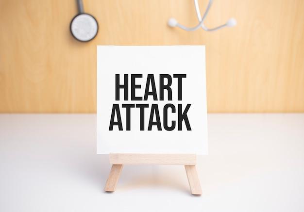 Знак сердечного приступа на небольшой деревянной доске на мольберте с медицинским стетоскопом