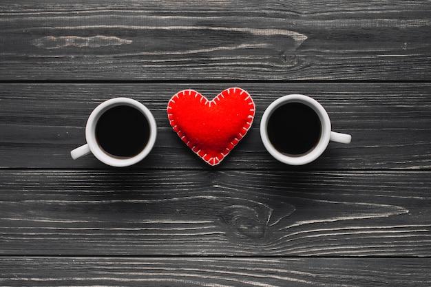 Сердце между чашкой кофе на сером фоне