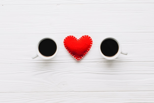 Сердце между чашками кофе