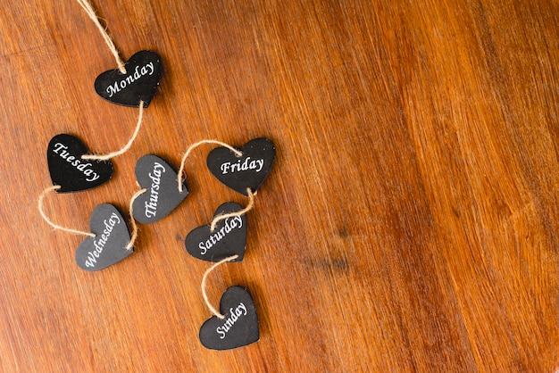 Heart of black wood with days of the weekend written on it.