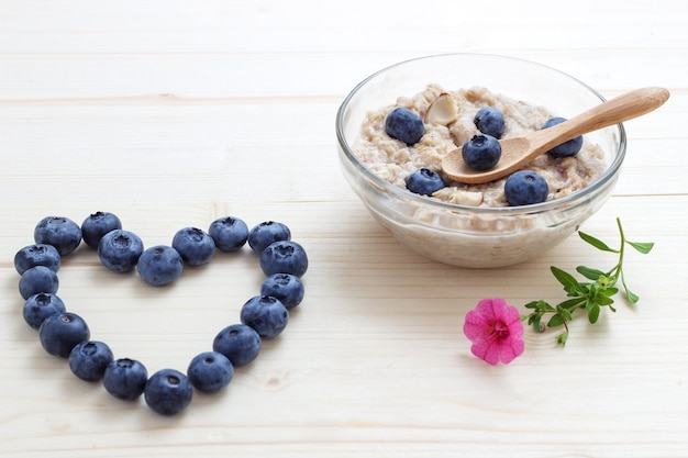 Heart of blueberries and oat flakes with blueberries and flowers.