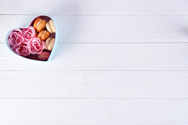 Heart box with macarons and rose on white wooden background, valentine's day