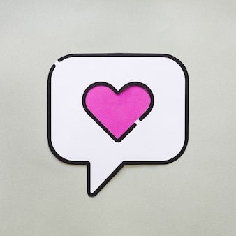Heart in bubble speech icon on grey table
