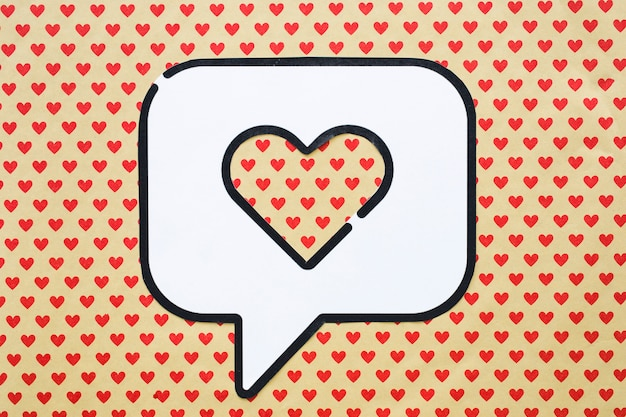 Heart in bubble speech icon on table with heart pattern