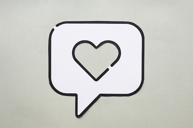 Heart in bubble speech icon on table