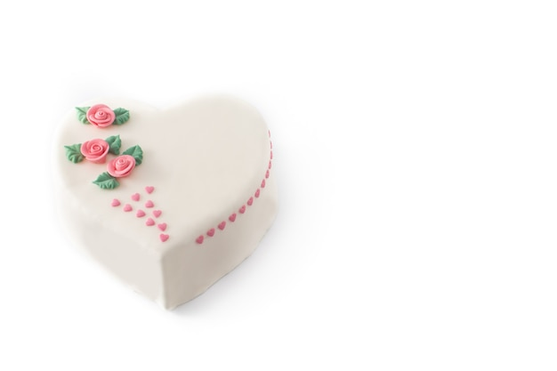 白い背景で隔離のバラとピンクの砂糖のハートで飾られた聖バレンタインデーのハートケーキ