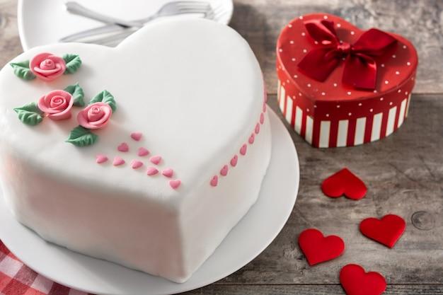 木製のテーブルにバラとピンクの砂糖のハートで飾られた聖バレンタインデーのハートケーキ