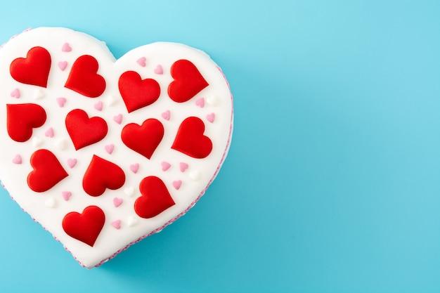 Сердечный торт на день святого валентина, украшенный сахарными сердечками на синем фоне
