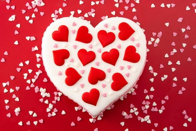Торт сердце на день святого валентина, украшенный сахарными сердечками на красном фоне