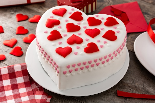 木製のテーブルに砂糖のハートで飾られた聖バレンタインデーのハートケーキ