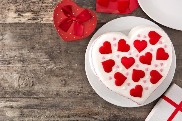 Торт-сердечко на день святого валентина, украшенный сахарными сердечками на деревянном столе