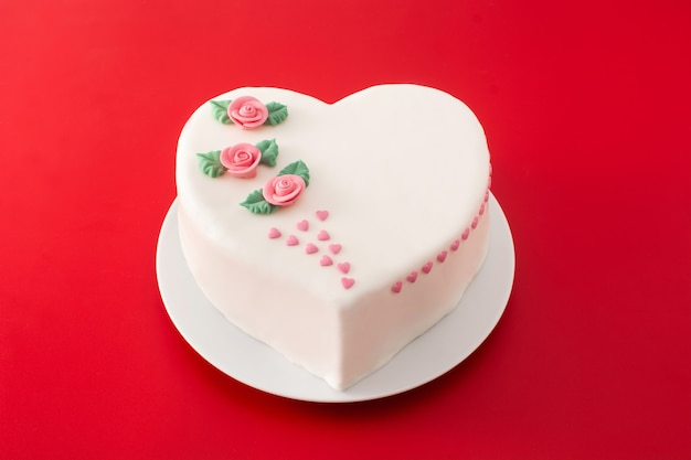 赤い背景にバラとピンクの砂糖のハートで飾られた聖バレンタインデー、母の日、または誕生日のハートケーキ
