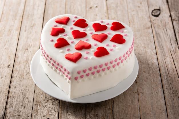 木製のテーブルに砂糖のハートで飾られた聖バレンタイン、母の日、または誕生日のハートケーキ