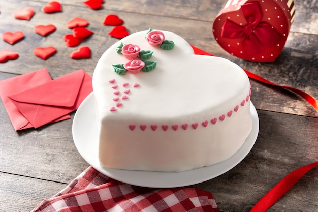 Heart cake for st. valentine's day,  decorated with roses and pink sugar hearts on wooden table