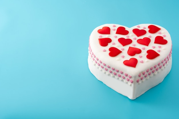 Heart cake for st. valentine's day,  decorated with sugar hearts on blue background