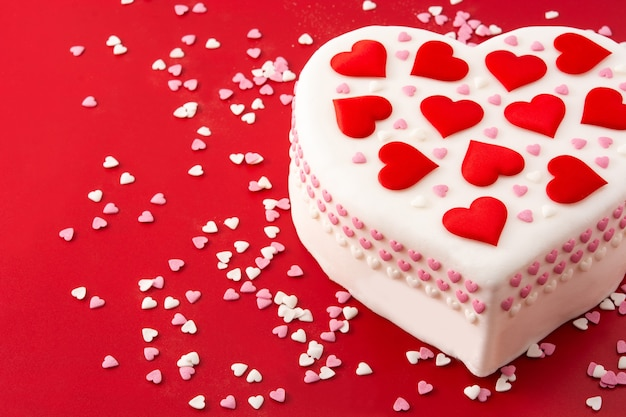 Heart cake for st. valentine's day,  decorated with sugar hearts on red background