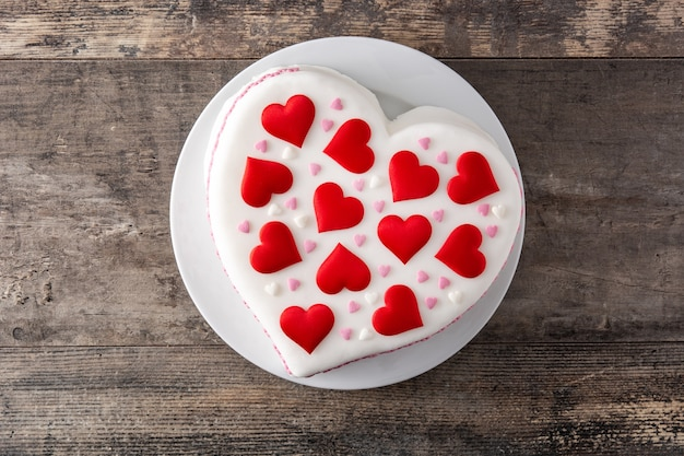 Heart cake for st. valentine's day,  decorated with sugar hearts on wooden table
