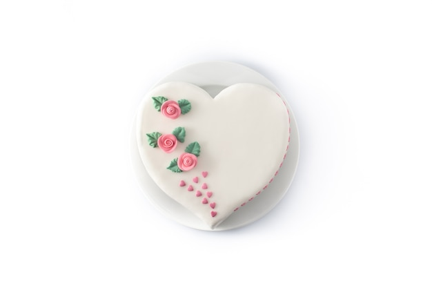 Heart cake for st. valentine's day, mother's day, or birthday, decorated with roses and pink sugar hearts isolated on white background
