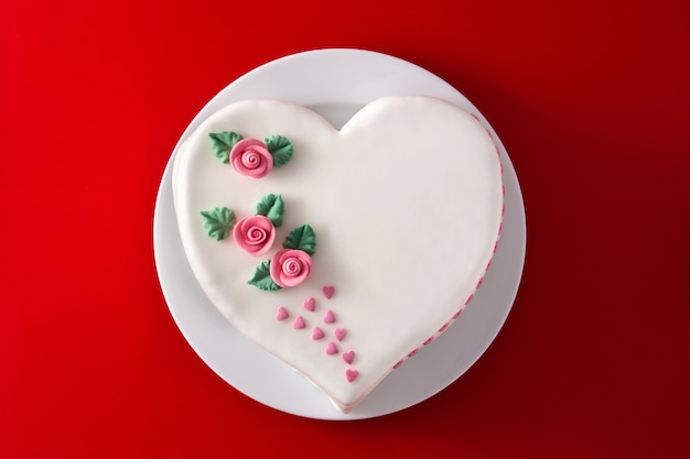 Heart cake for st. valentine's day, mother's day, or birthday, decorated with roses and pink sugar hearts on red background