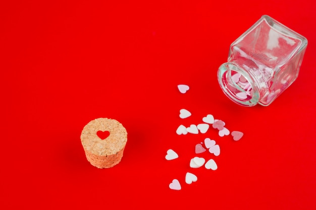 Heart candies scattered from jar