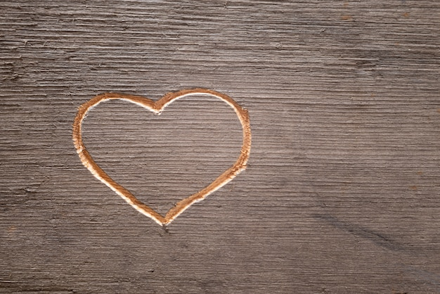 Heart carved on the wooden plank.