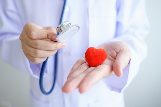 Проверка сердца доктор держит красное сердце на руках в офисе больницы. здравоохранение и медицинская концепция.