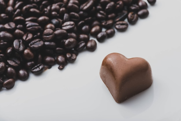 Heart of chocolate next to coffee beans