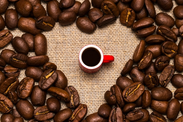Heart of coffee beans and a cup on burlap Premium Photo
