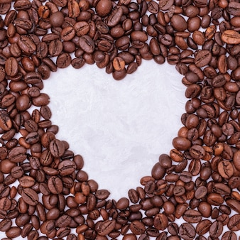 Heart coffee frame made of coffee beans on white stucco background, top view, copy space