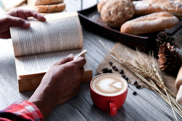 Heart coffee in red cup with people reading a book.