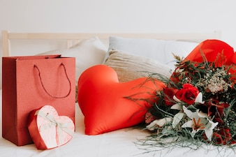 Heart cushion between gift and bouquet