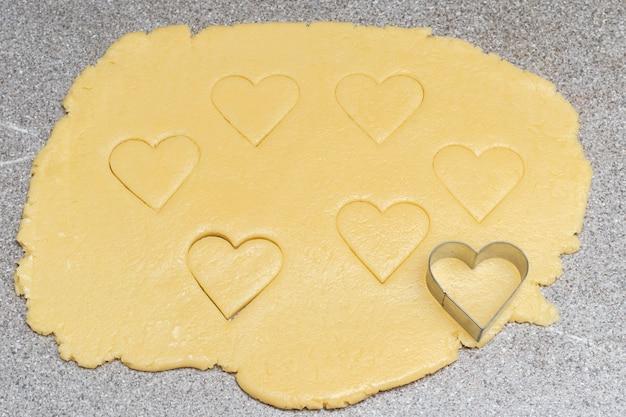 灰色のテーブルの表面に黄色い生の生地を切るためのハートカットクッキーとハートの形。