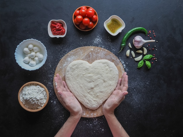Heart of dough in the hands. top view.