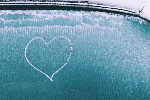 Heart drawn on frozen iced car window