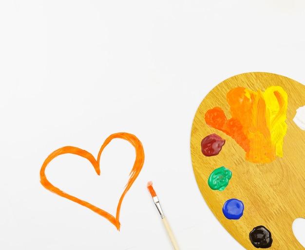 Сердце, нарисованное гуашью, палитра на белом фоне, с копией пространства.