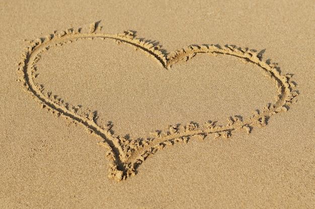 砂に描かれた心。ビーチの背景。上面図