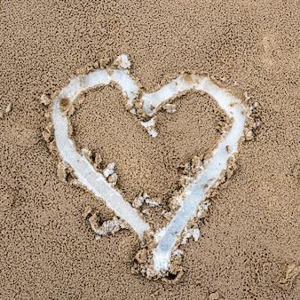 Сердце нарисовано на песке. вид сверху. под песком лежит снег.