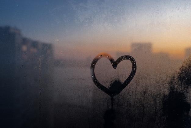 Heart drawn on moisturized glass window