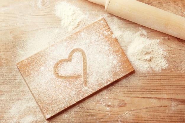 小麦粉に描かれたハートと木製のテーブルの背景に麺棒