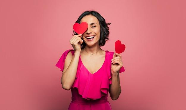 Сердце-глаза. фотография крупным планом обрадованной женщины в фиолетовом платье, которая держит в руках две открытки с валентинками, прикрывает одной глаз и смеется.