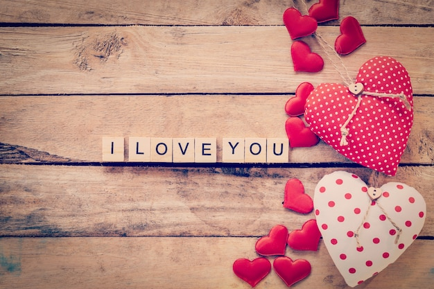 Heart fabric frame and wooden text i love you on wooden table background.