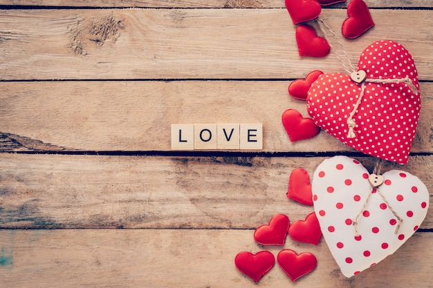 Heart fabric frame and wooden text love on wooden table background.