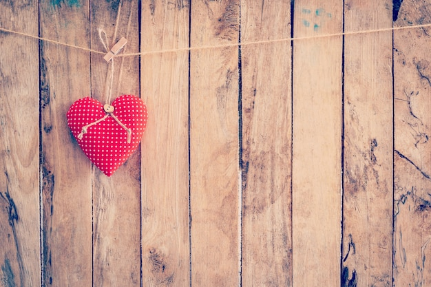 Heart fabric hanging on clothesline and wood background with space.